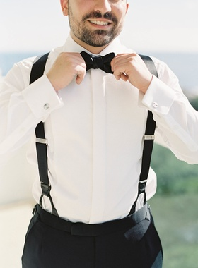 Groom in tuxedo pants, suspenders, white shirt, and black bow tie tightening tie