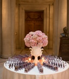Wedding reception escort card table with ornate white urn, pink roses, hydrangeas