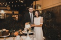 bride in givenchy wedding dress short sleeve with groom cakes with orange flowers outdoor reception