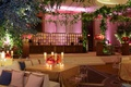 Wedding weekend welcome dinner decorated with greenery, candles and orange and pink flowers