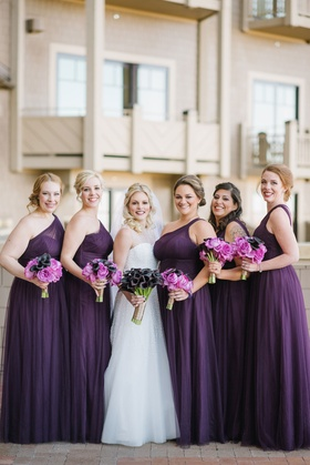 Bride in Reem Acra wedding dress with calla lily bouquet and bridesmaid dresses purple one shoulder