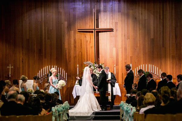 Bride and groom in large church in front of cross