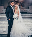 bride in lazaro mermaid wedding dress long blonde hair veil white bouquet with groom in suit white