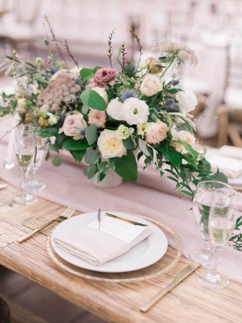 wedding reception wood tablee low centerpiece white dusty rose lavender blue greenery gold flatware