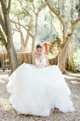 bride in lazaro ball gown with crystal adorned waist and spaghetti straps