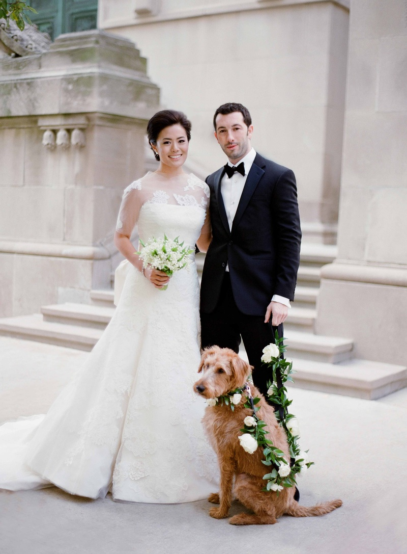 Bride in Vera Wang wedding dress holding bouquet lily of the valley groom tuxedo dog with leash