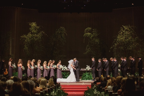 trees brought into church ceremony wedding dark with red carpet