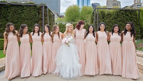 Bride in middle of ten bridesmaids in long blush light pink gowns