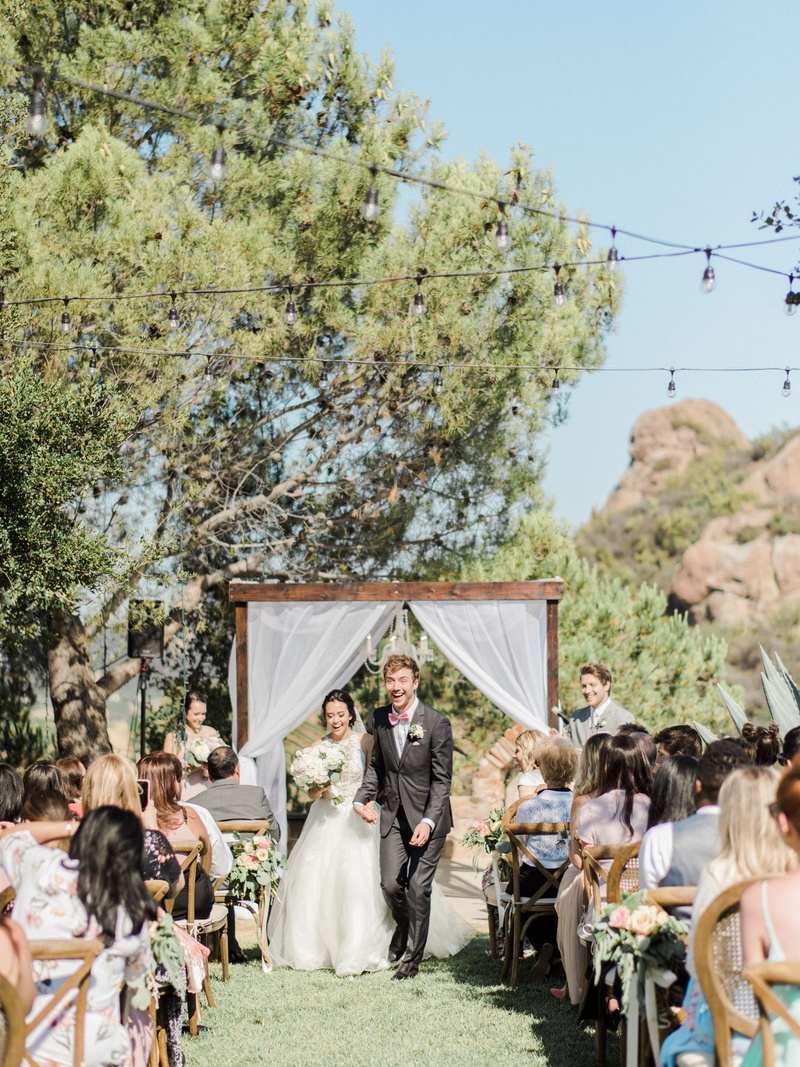 Megan Nicole Flores and Cooper Green outdoor daytime wedding ceremony malibu wood arbor guests
