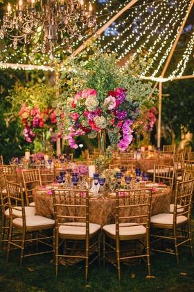 Tent wedding reception with gold rosette table linens, tall green flower arrangements, string lights