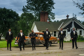 groom and groomsmen in black suits in front of rusted vintage car