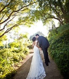 Bride in a Casablanca Bridal lace gown kisses groom in a dark suit