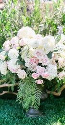 Ceremony flower arrangement in urn with pink rose, white hydrangea, and white dahlia flowers