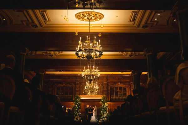 wedding ceremony at the willard in washington dc chandelier wood paneling ceiling greenery chuppah
