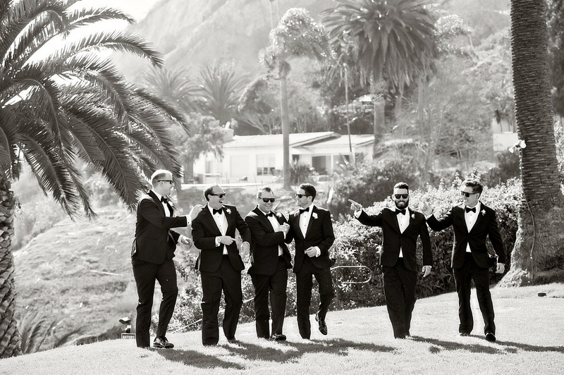 black and white photo of groomsmen pointing groom golf course palm trees california wedding