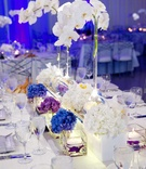 White orchid in bulb vase with floating candles at reception