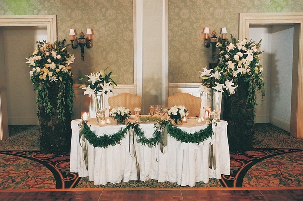 Hotel ballroom sweetheart table with green garlands
