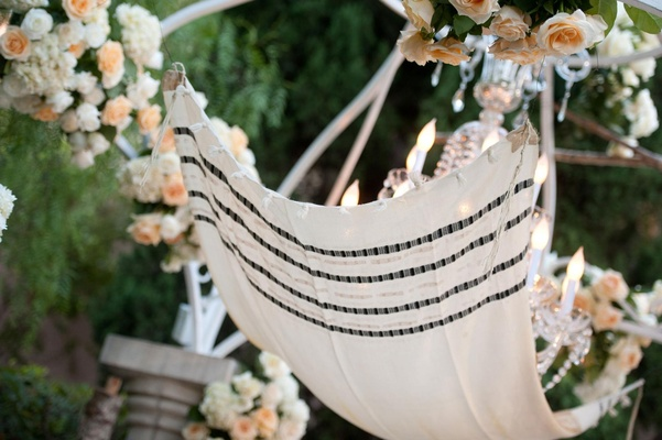 Sentimental tallit suspended from peach rose gazebo