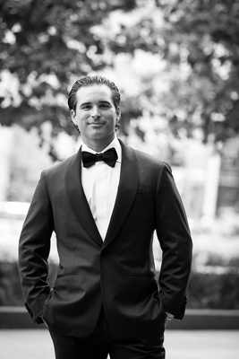 Black and white photo groom in tuxedo and bow tie with slicked back hair in New York City