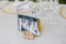 Wedding head table with photo sign of the bride, groom, and their dog propped by wine corks