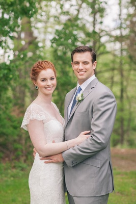 Redhead wearing ivory gown and man in grey suit