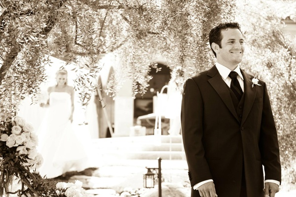 Black and white photo of groom waiting for bride