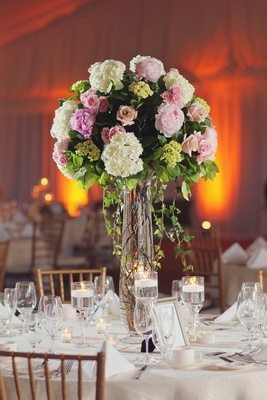 White table topped with towering flower arrangement
