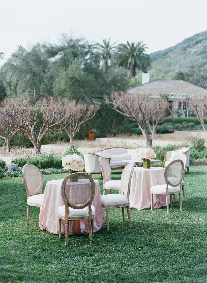 Green lawn with pink cocktail table linen, rustic round back hairs, at San Ysidro Ranch