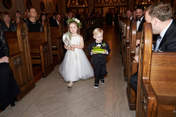Flower girl in white dress with flower crown and wand and ring bearer in little suit with green mum