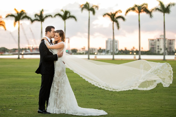 wedding portrait bride and groom in palm beach palm trees sunset lace trim cape instead of veil