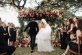 wedding ceremony jewish outdoor greenery pink coral orange flowers guests in wood chairs