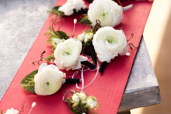 Groomsmen ranunculus blossom wedding boutonniere styles on red cardboard