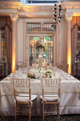 Wedding reception table with white and pink flowers surrounding a vase with a floating candle