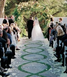 Bride and groom stand at end of stone and grass patterned aisle