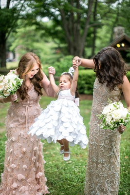 bridesmaids in mismatch dresses with bouquets holding hands with flower girl white flower girl dress