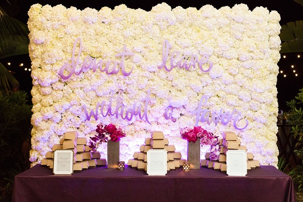 white hydrangea wall with donut doughnut message purple text calligraphy purple table linens flowers