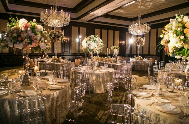 The reception venue and decor with flowers chandeliers glassware and candles