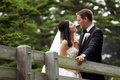 Bride and groom look into each other's eyes on bridge