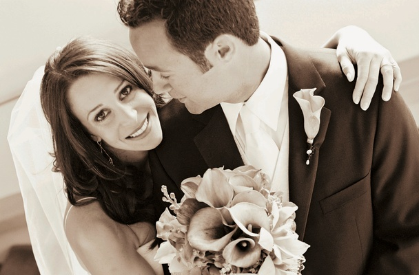 Sepia tone image of bride with calla lily bouquet and groom