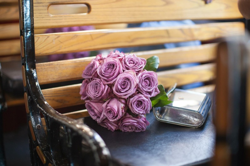 Violet roses and silver purse on trolley seat