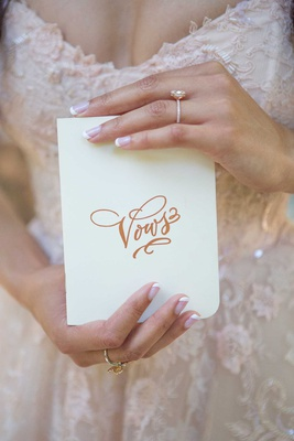 bride with engagement ring and french manicure holding vows book white book gold calligraphy