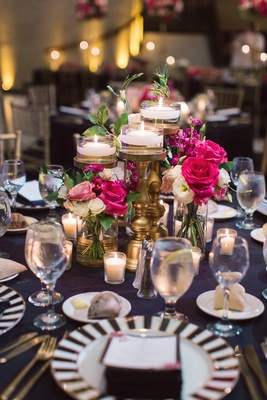 floating candles on gold stands, bright pink roses, black and white wedding decor