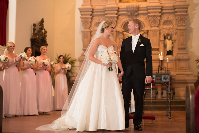Bride in Anne Barge ball gown and veil with groom in black tuxedo at Brophy Chapel