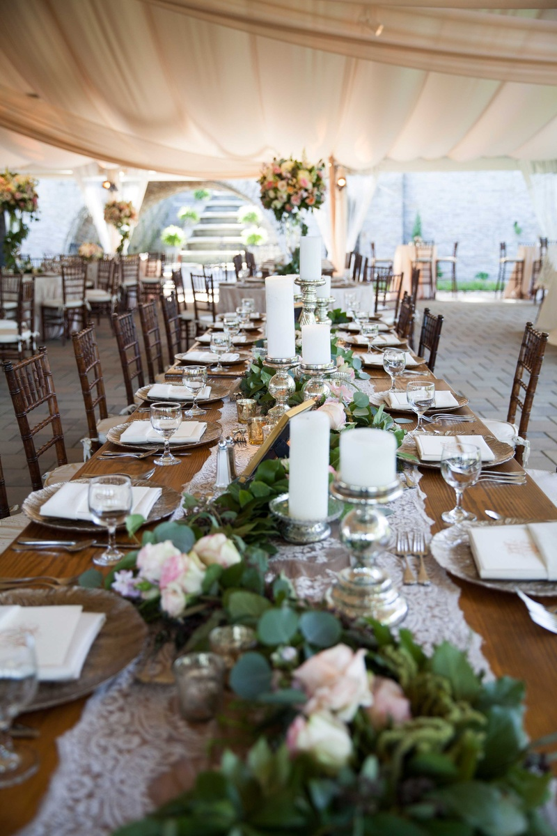 long wooden table with white lace runner on top of verdant runner with foliage and flowers