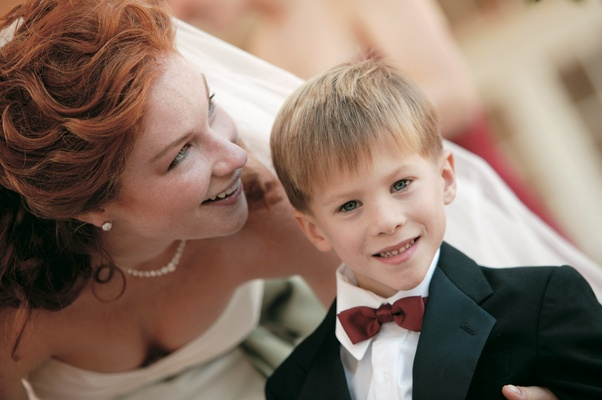Bride with ring bearer in tux and red bow tie