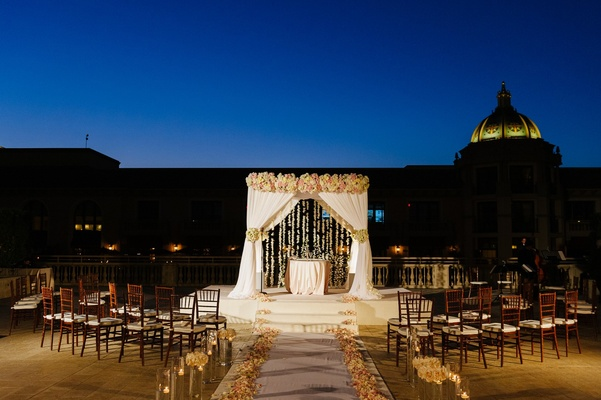 chuppah with white drapery, blush and ivory roses, and hanging orchids, lighting, night ceremony