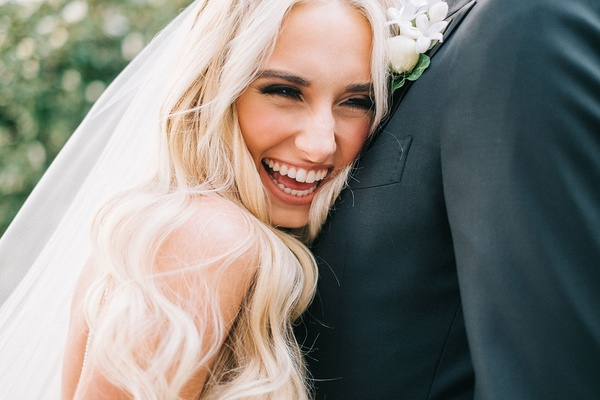 Bride smiling large smile while hugging groom long blonde hair veil groom boutonniere