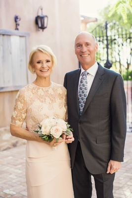 Mother of bride in lace mother of bride dress with half sleeves tier skirt at hips holding bouquet