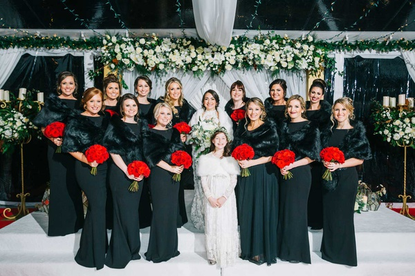 bride with bridesmaids in black dresses fur wraps bright red bouquet flower girl in long sleeves