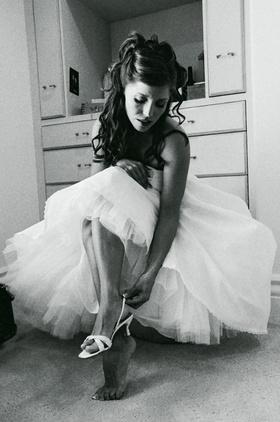 Bride fastening wedding shoes